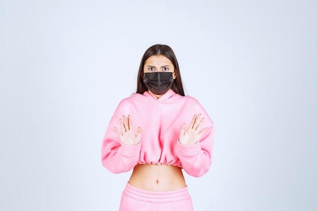 Ragazza che indossa la sua maschera nera e ferma il virus.