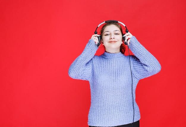 ヘッドフォンを付けて音楽を聴いている女の子。
