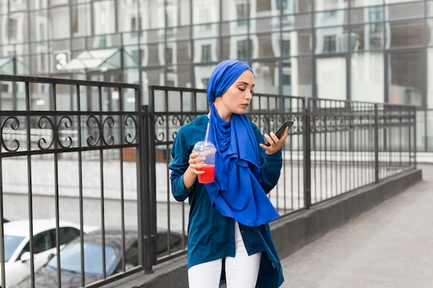 Girl wearing a hijab and holding a smoothie while looking at her phone