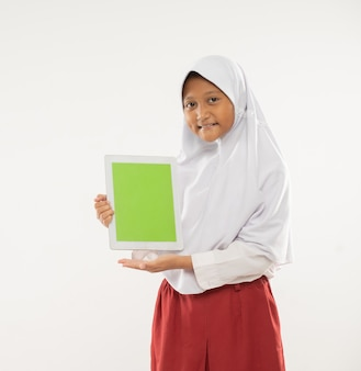 A girl wearing a hooded elementary school uniform stands holding a digital tablet and showing the ta...