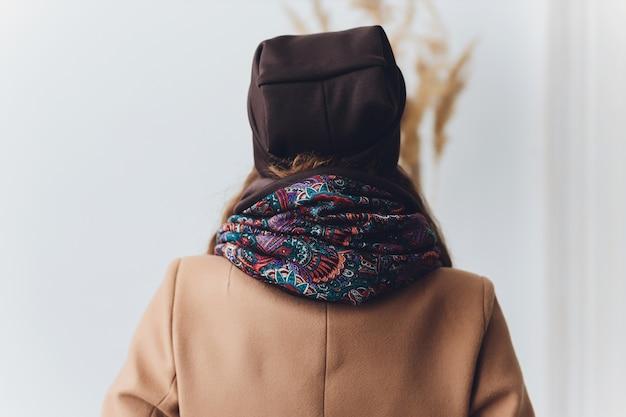 暖かいニットの帽子、コート、スカーフを身に着けている女の子