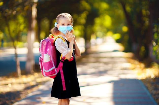 マスクとバックパックを着ている少女