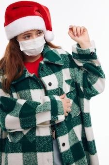Девушка в новогодней одежде медицинская маска праздник рождества светлый фон. фото высокого качества