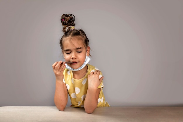 Girl wearing off her medicine respirator mask and eating chocolate bars with pleasure
