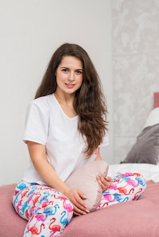 Девушка в пижаме позирует на кровати