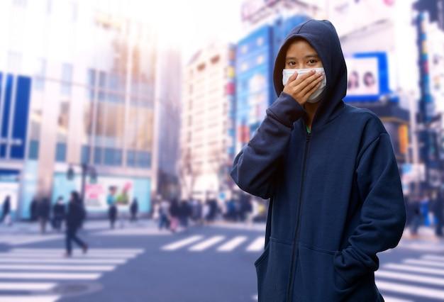 도시에서 코로나 바이러스에 대한 보호 얼굴 마스크를 착용하는 여자