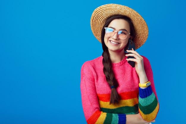 Девушка в радужном свитере и соломенной шляпе разговаривает по телефону