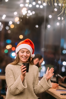 Girl wearing santa claus hat sitting in coffee shop and drinking coffee