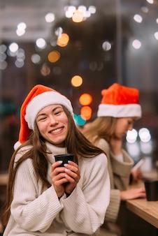 커피 숍에 앉아 커피를 마시는 산타 모자를 쓰고 소녀