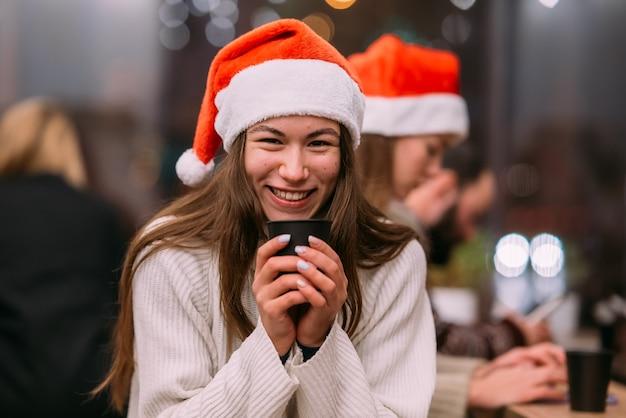 コーヒーショップに座ってコーヒーを飲むサンタの帽子をかぶっている女の子