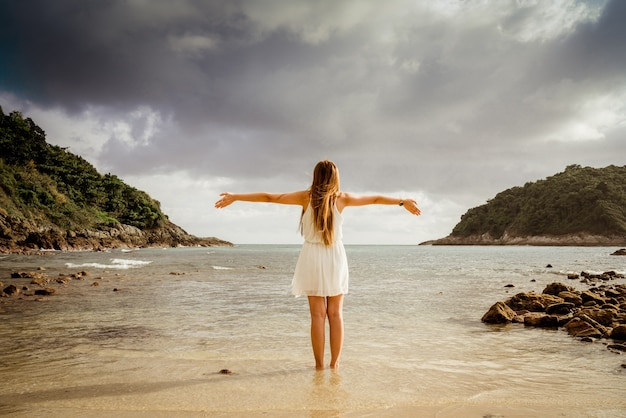 Girl wearing a sea cap standing on the beach, clear sky, beautiful sea for relax