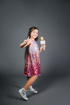 Girl wearing sequin dress holding microphone showing victory sign against gray background