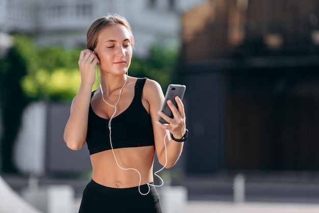 Girl  wearing in sportswear in earphones holding a smartphone and looking at the screen