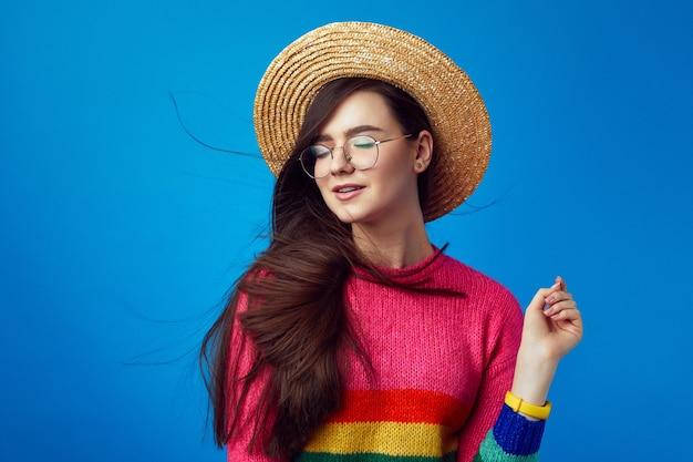Девушка в соломенной шляпе закрывает глаза от удовольствия, пока ветер развевает волосы