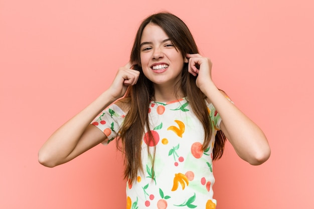 Girl wearing a summer clothes against a red wall covering ears with hands.
