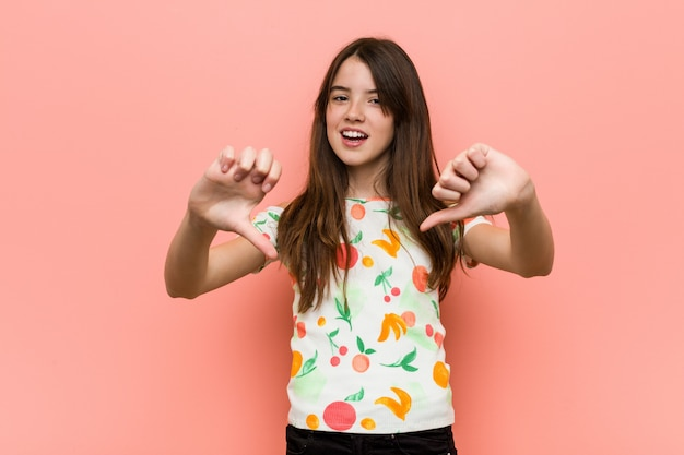 Girl wearing a summer clothes against a red wall showing thumb down and expressing dislike.