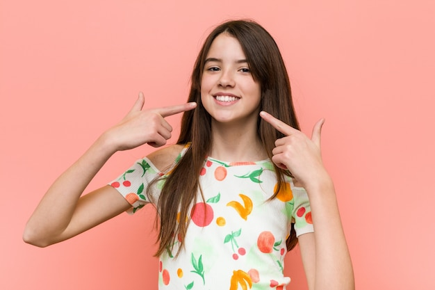 Girl wearing a summer clothes against a red wall smiles, pointing fingers at mouth.