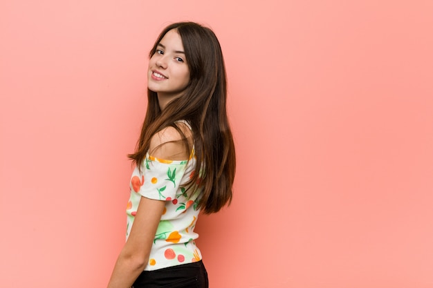 Girl wearing a summer clothes against a  wall looks aside smiling, cheerful and pleasant.
