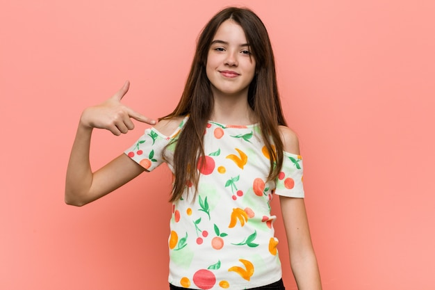 Girl wearing a summer clothes against a  wall person pointing by hand to a shirt copy , proud and confident
