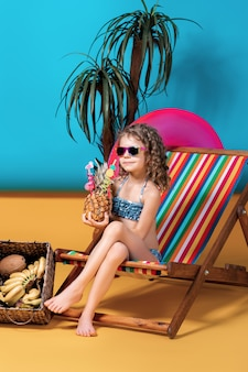 Girl wearing sunglasses and swimsuit sunbathing in rainbow deck chair