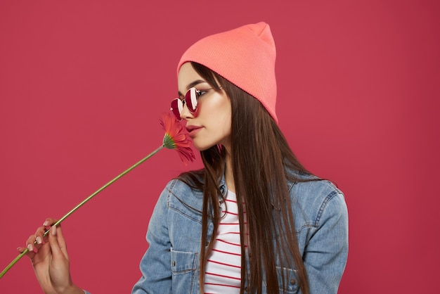 Девушка в солнцезащитных очках в розовой шляпе с красным цветком мода позирует романтика