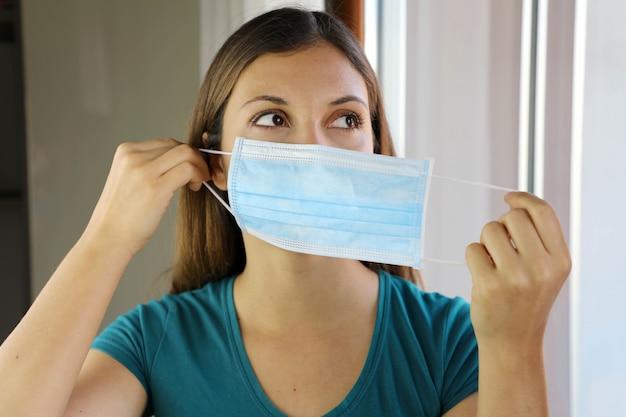 Девушка в хирургической маске на лице от коронавирусной болезни 2019.