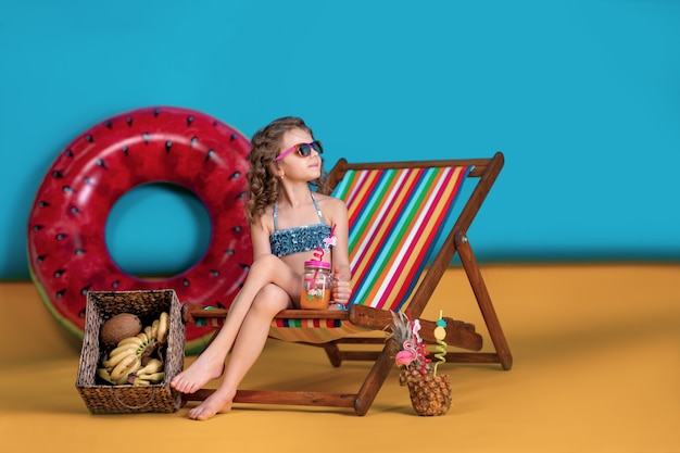 Girl wearing swimsuit, sunglasses holding jar with juice or cocktail with multicolored straws sitting in rainbow deck chair by big watermelon inflatable circle and looking away