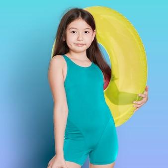 Girl wearing swimwear holding a inflatable tube