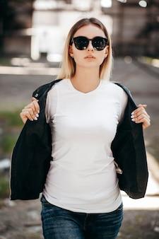 Tシャツ、メガネ、革のジャケットを着た女の子が通りに対してポーズ