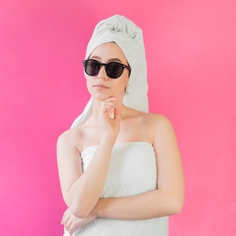 Girl wearing a towel and sunglasses