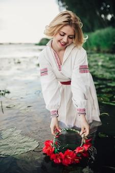 花の花輪と水の伝統的なウクライナのドレスを着て少女