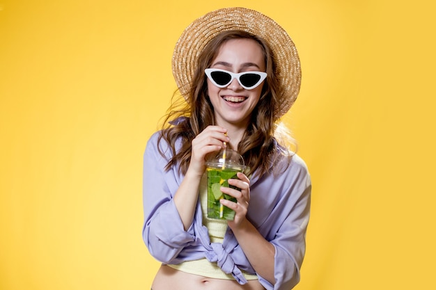 Girl wearing a trendy sunglasses while drinking a mojito cocktail