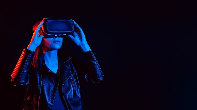 Girl wearing virtual reality glasses with red and blue lights on black background