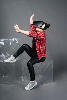 仮想現実を身に着けている女の子は空気中の彼女の手に触れるゴーグル