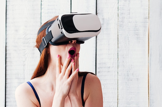 A girl wearing vr glasses, excited, holding her hands at face, pink lips and nails