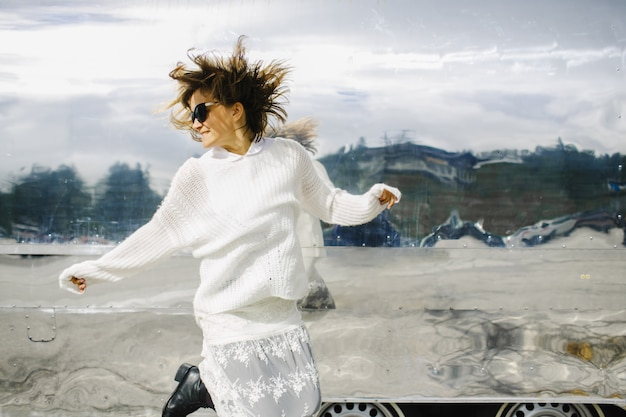 Girl wearing white clothes jumps next to glimmering vehicle