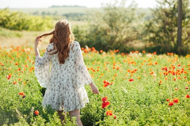 白いドレスと麦わら帽子をかぶった女の子は、夕日に赤いポピーの花の間を歩きます。若い女性は、赤い花でいっぱいのフィールドで良い天気と楽しんで楽しんでいます。春と自然の概念