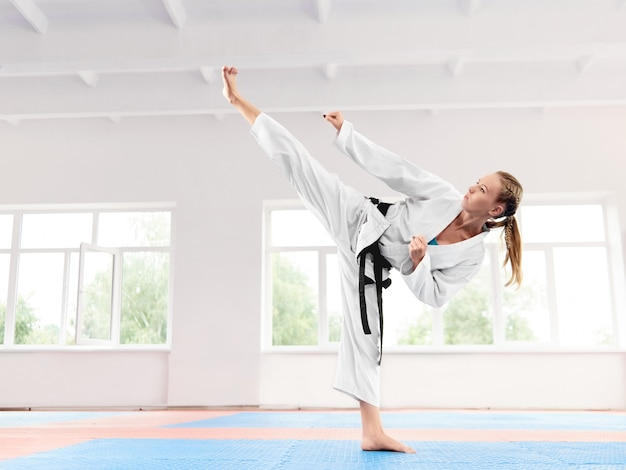 Girl wearing in white kimono performing martial arts high kick skill.