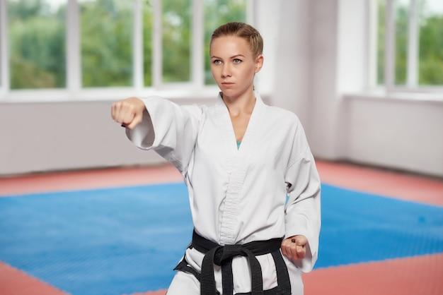 Girl wearing in white kimono with black belt standing in karate pose.
