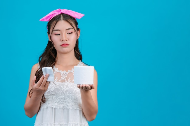 Girl wearing white pajamas holding a rolltissue paper in the hand on the blue .
