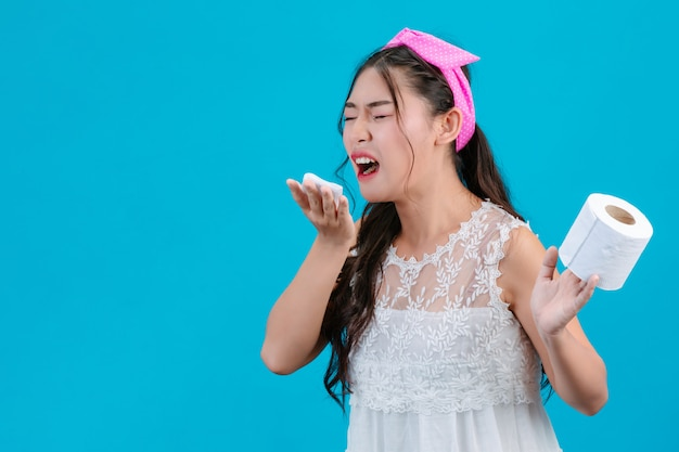 The girl wearing white pajamas is not comfortable. using tissue to wipe her nose on a blue .