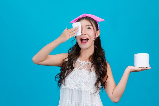 Girl wearing white pajamas using tissue paper on her face on a blue .