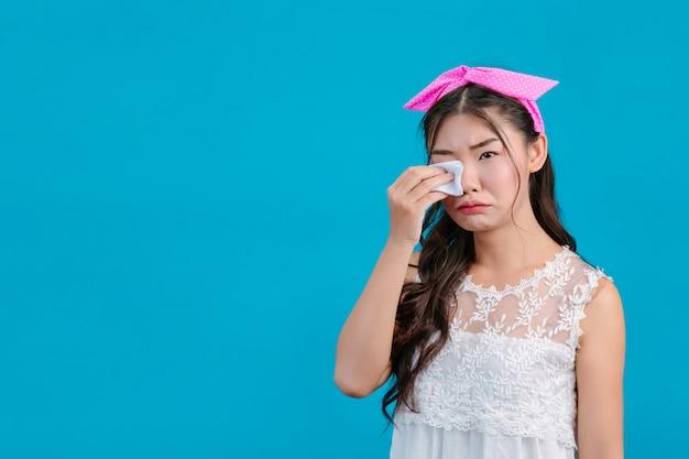 흰색 잠옷을 입고 소녀 파란색에 그녀의 얼굴에 휴지를 사용합니다.