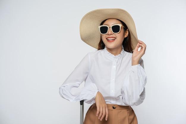 Ragazza che indossa una camicia bianca e pantaloncini che indossa un cappello indossare occhiali e manico sul cappello