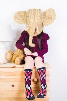 고리 버들 코끼리 마스크를 테이블에 앉아 입고 소녀