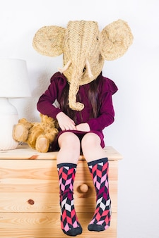 Girl wearing wicker elephant mask sitting on table