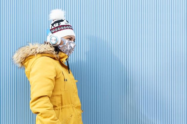 冬の服と青い壁に沿って歩くフェイスマスクを身に着けている女の子。
