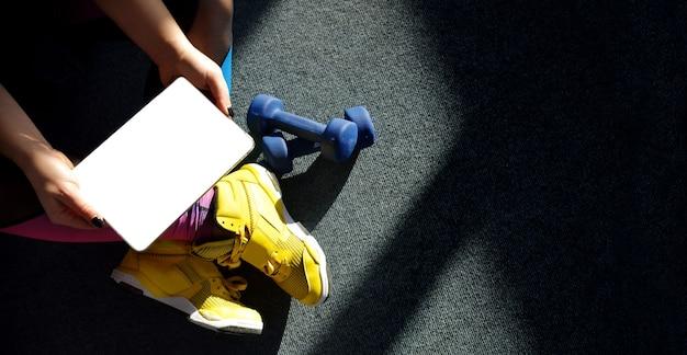 노란색 운동화를 입고 소녀는 훈련을 위해 무게와 태블릿을 보유하고 있습니다. 온라인 학습 개념.