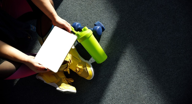 Girl wearing yellow sneakers holds a tablet with weights and a bottle of water around for training. online learning concept.