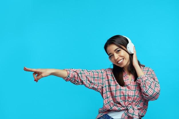 Девушка в наушниках слушает музыку, у нее веселое выражение лица